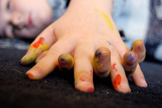 a small child's hands, clasped, with patches of red, yellow, and blue paint