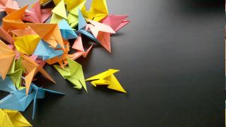 A pile of paper cranes, in different colors, on a black surface