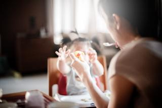 A parent, holding food on a spoon, in front of a toddler reaching.