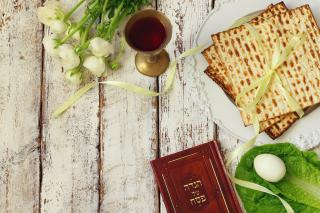 From above, an artful arrangement of tulips, a Hebrew prayer book, matzoh, egg, and cup of wine.
