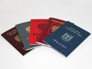 Five passport booklets issued by different nations are fanned out so the covers in different alphabets and languages are displayed.