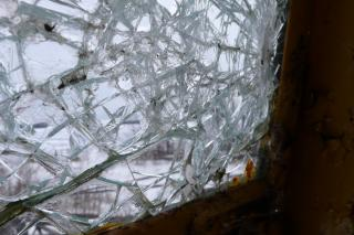 A thick pane of glass is shattered, with hundreds of radiating cracks