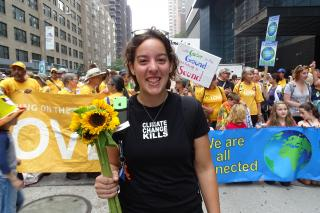 Young woman holding sunflowers with more UUs in background at 2014 People's Climate March in New York City.