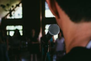The back of a person's head as they speak into a microphone; in front of them, a blurred line of people