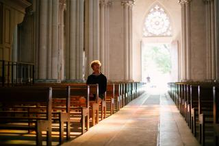 In a sunlit sanctuary, a person sits in a wooden pew.