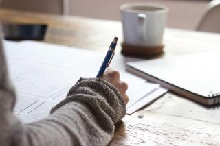 A table covered by papers, a notebook, and a coffee mug-- and a person's hand, writing with a pen.