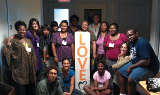 "Group of 15 youth and young adults of color gather around a sign with the word ""Love"" on it."