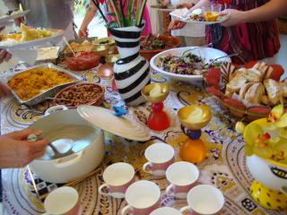 A table filled with cups, casseroles, and soup being ladled out