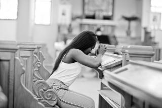 In a church pew, a Black woman leans forward with her hands clasped in prayer.
