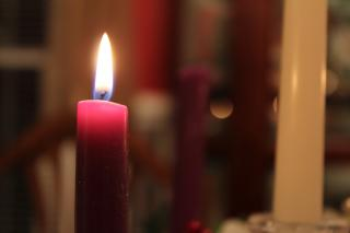 A purple taper candle, lit, with other taper candles blurred in the background.