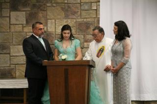 At a church pulpit, a quinceañera (a girl who is turning 15) in a formal dress, with her parents and a priest.