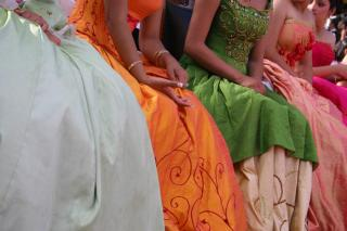 A row of young women, visible only from their shoulders to their ankles, in long colorful gowns.