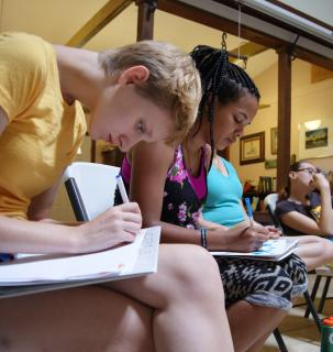 a young white woman is concentrated on writing on a piece of paper in the foreground and behind her a young black woman is doing the same thing