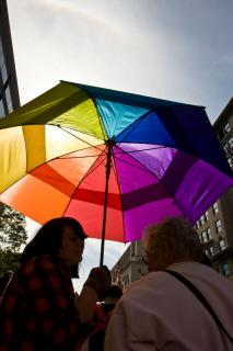 Woman holding rainbow patterened umbrella at LGBTQ Equality March, October 2009.