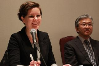 Ray Acheson, at left, smiles and speaks into a microphone. To her right sits Hiro Sakurai, another panelist.