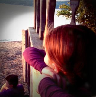 A retro-style photo of a child looking from a porch toward a calm lake while an adult sits below also gazing at lake