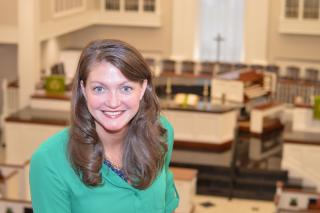 A smiling Rev. Lori Walke, with a church chancel and pews behind her