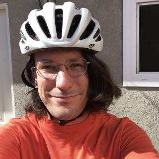 Headshot photo of Rev. Stevie K. Carmody smiling and wearing a bike helmet