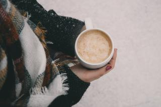 Seen from above, a person's hands cradle a mug of cocoa. Also visible is their torso wrapped in a wool blanket.