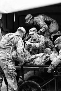 A team of military soldiers in camo tends to a person on a stretcher.