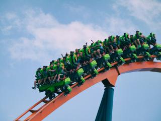 Against a blue sky, people on a roller coaster are harnessed in and beginning to descend a steep slope