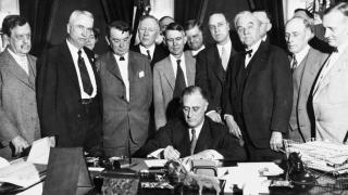 Photo of President Franklin Delano Roosevelt signing the Tennessee Valley Authority Act into Law, surrounded by advisers