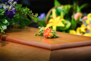 A rose resting on a wooden casket, more flowers visible in the background