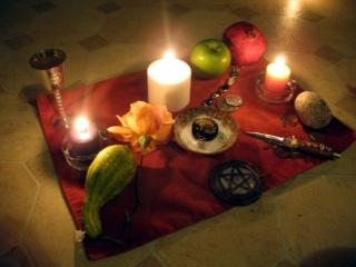 A pagan altar arrayed on a red cloth: candles, a gourd, an apple, a pomegranate, and the ritual knife and pentagram associated with Wicca