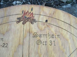 "An arc of a wooden wheel, with ""Samhain Oct 31"" carved into it, along with a bonfire."