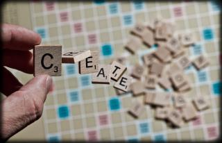 "In the background, letters are piled on a Scrabble board. In the foreground, someone holds the ""C"" tile as the letters ""R E A T E"" fall towards the board."