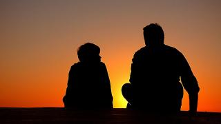 Silhouette of a adult and child in front of a sunrise/sunset