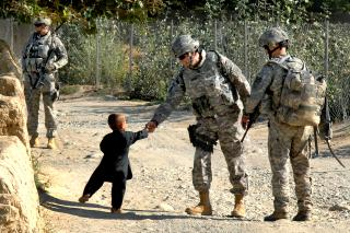 U.S. Army Lt. Col. Jeff Cantor shakes the hand of an Afghan boy outside Bagram Airfield in Janquadam, Parwan province, Afghanistan