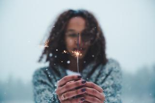 In the snow, with only their upper body visible, a person holds a lit sparkler.