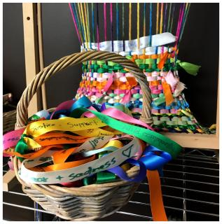Basket of colorful ribbons with words expressing emotions in front of loom with woven ribbons