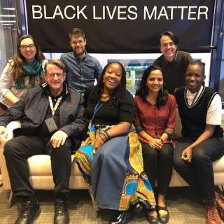 "Photo of the UUA's International Staff group at their 2019 staff group retreat, sitting in front of a ""Black Lives Matter"" sign."