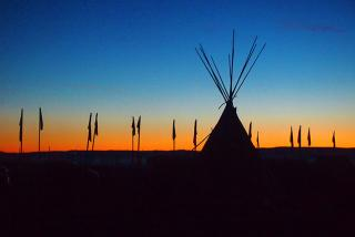 Against a band of vivid orange sunset and deep blue sky, the silhouette of a teepee and flags