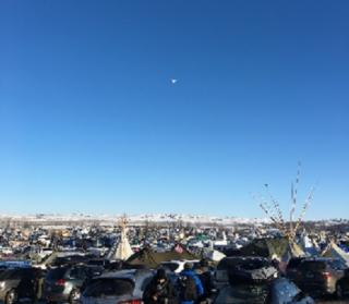 Standing Rock, North Dakota encampment showing cars, tipis, and people, with a large blue sky above that has a drone aircraft flying through it