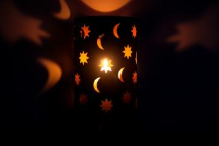 A lantern with moon and star shapes casting light onto dark walls.