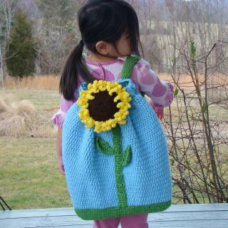 A small child, back to the camera, wearing a handmade crocheted blue backpack with a large sunflower on it.
