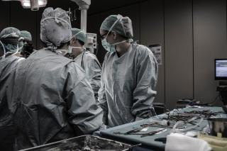 In an operating room, several sugeons in blue scrubs look at a patient off-camera.