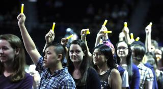 Young adults, of different styles and races, stands in a line holding up glo-sticks.
