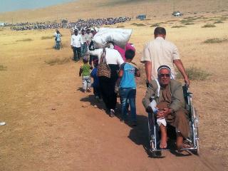 A long line of Syrian Kurdish refugees travel across a parched field intoto Turkey