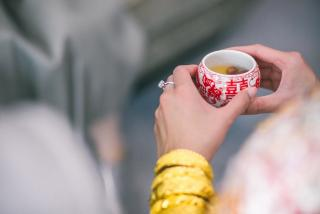 A woman's hands -- on which there is a large wedding ring -- hold a cup, with Chinese characters on the sides, containing tea..