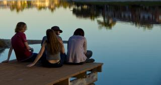 On a dock extending into a smooth pond, four teenagers sit.