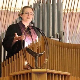 In a clerical robe and stole, Heather gestures as she speaks in a pulpit with a chalice in the foreground