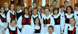 A group of young Unitarians from the Transylvania region of Romania smile, wearing traditional ethnic clothes.