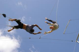 The camera gazes up at a blue sky, where a trapeze artist, flying through the air, holds her arms out to be caught by the catcher (also on a trapeze)