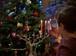 A parent and child kindle their menorah in front of their Christmas tree.