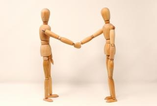 Two wood artists mannequins shaking hands
