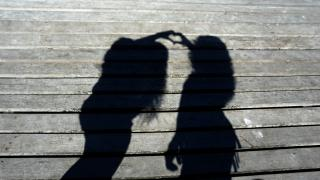 The shadowed silhouettes of two people holding their hands together to form a heart.